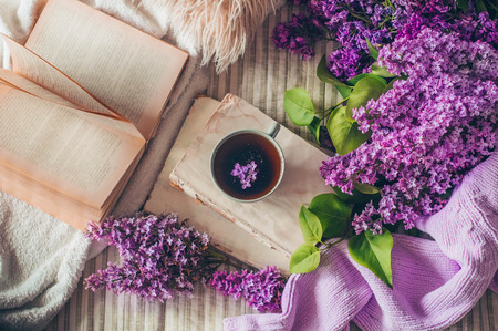 Still life details in home interior of living room. Sweaters and cup of tea with lilac flowers and spring decor on the books. Read, Rest. Cozy spring concept.