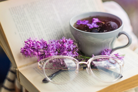Book, glasses, cup of tea and lilac on a wooden window. Fragrant tea in the garden. Romantic concept. Vintage style