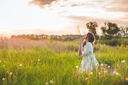 Girl closed her eyes, praying in a field during beautiful sunset. Hands folded in prayer concept for faith, spirituality and religion. Peace, hope, dreams concept Stock Photo