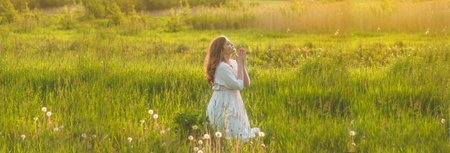 Girl closed her eyes, praying in a field during beautiful sunset. Hands folded in prayer concept for faith, spirituality and religion. Peace, hope, dreams concept Banco de Imagens - 123743783