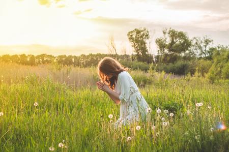 Niña cerró los ojos, rezando en un campo durante la hermosa puesta de sol. Manos juntas en concepto de oración por fe, espiritualidad y religión. Paz, esperanza, concepto de sueños