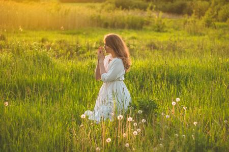 La ragazza chiuse gli occhi, pregando in un campo durante il bellissimo tramonto. Mani giunte nel concetto di preghiera per fede, spiritualità e religione. Concetto di pace, speranza, sogni Archivio Fotografico