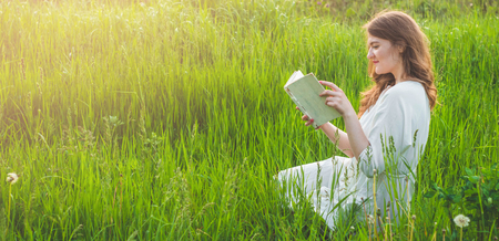 Beautiful girl in field reading a book. The girl sitting on a grass, reading a book. Rest and reading. Outdoor reading.