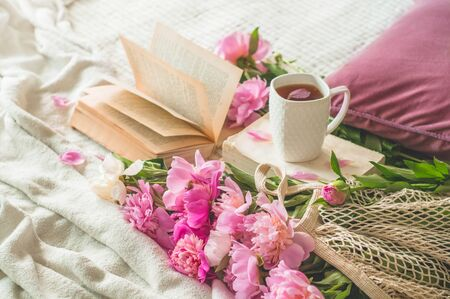Still life details in home interior of living room. Cup of tea with Pions flowers and spring decor on the books. Read, Rest. Cozy spring concept.