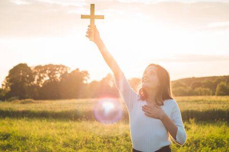 Teenager-Mädchen, das ein Kreuz in der Hand während des schönen Sonnenuntergangs hält. Hände gefaltet im Gebetskonzept für Glauben, Spiritualität und Religion. Frieden, Hoffnung, Traumkonzept