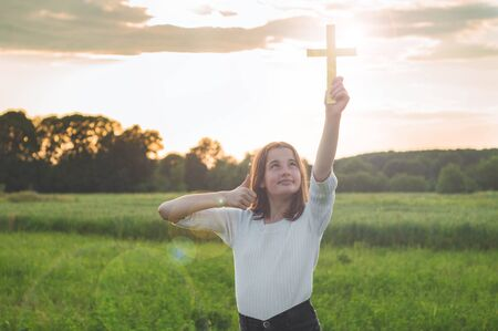 Teenager Girl holding a the cross in hand during beautiful sunset. Hands folded in prayer concept for faith, spirituality and religion. Peace, hope, dreams concept