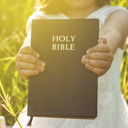 La ragazza cristiana tiene la bibbia nelle sue mani. Leggere la Sacra Bibbia in un campo durante il bellissimo tramonto. Concetto di fede, spiritualità e religione. Pace, speranza