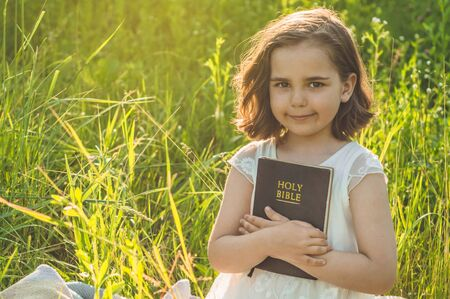 Christian girl holds bible in her hands. Reading the Holy Bible in a field during beautiful sunset. Concept for faith, spirituality and religion. Peace, hope