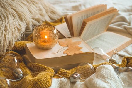 Sweet Home. Still life details in home interior of living room. Sweaters and candle,  autumn decor on the books. Read, Rest. Cozy autumn or winter concept. Stock Photo