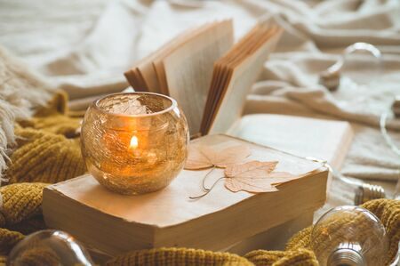 Sweet Home. Still life details in home interior of living room. Sweaters and candle,  autumn decor on the books. Read, Rest. Cozy autumn or winter concept. 스톡 콘텐츠 - 130201959