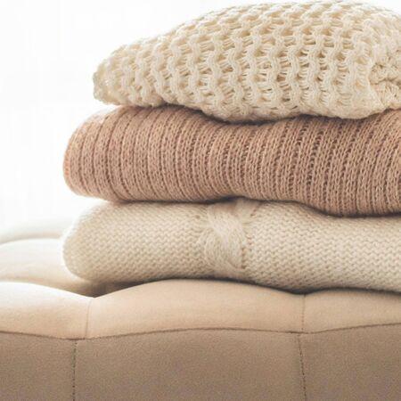 Una pila de suéteres de punto en el interior de la sala de estar. El concepto de confort otoño invierno