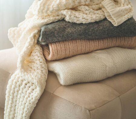Une pile de pulls tricotés à l'intérieur du salon. Le concept de confort automne hiver