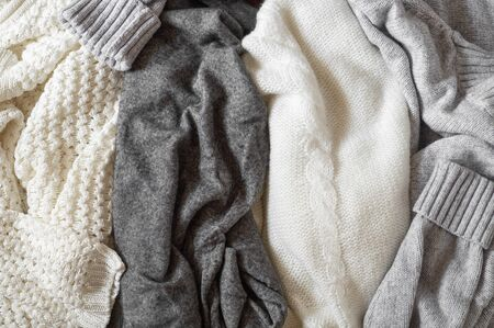 Fall Background with warm sweaters. Pile of knitted clothes. Warm background, knitwear, space for text, Autumn winter concept. Copy Space.