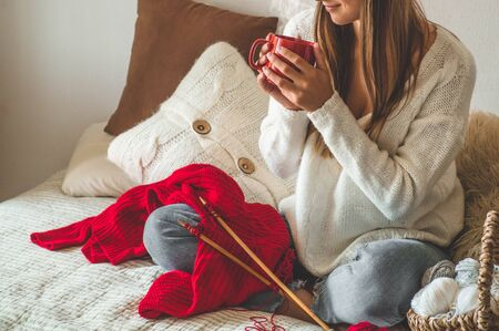 Beautiful girl knits a warm sweater with a hot cup of tea on the bed. Knitting as a hobby. Accessories for knitting.