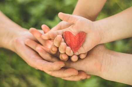 Childs hand and old hand grandmother hold heart. Concept idea of love family protecting children and elderly people grandmother friendship togetherness relationship Two generation. Stock fotó