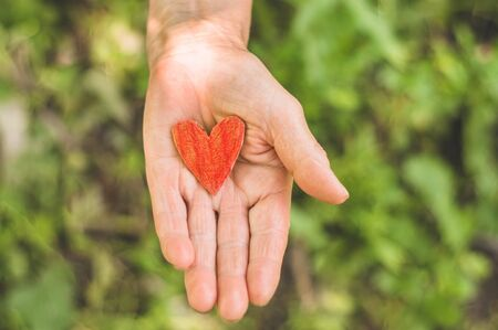 Old hand grandmother hold heart. Concept idea of love family protecting elderly people grandmother friendship togetherness relationship.