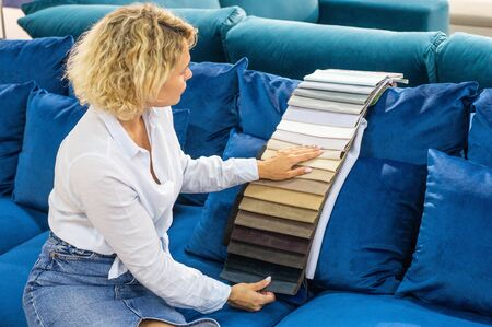 A young women looks at tissue samples. Selects the color of the sofa. Textile industry background.
