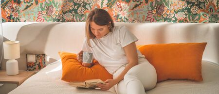Attractive young woman is reading a book at home. Thoughtful girl reading important book. Reading and development