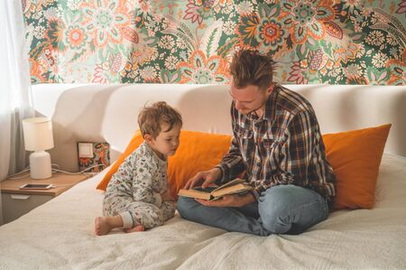 Dad and Son read a book together, smiling and hugging. Family holiday and togetherness. Happy fathers day.