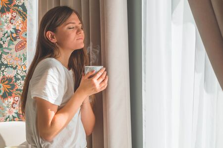 Woman with cup of hot drink by the window. Looking at window and drink tea. Good morning with tea. Autumn Winter Time. Cozy home. Stock Photo