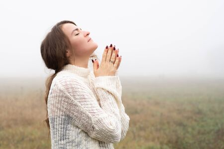 Girl closed her eyes, praying in a field during beautiful fog. Hands folded in prayer concept for faith, spirituality and religion. Peace, hope, dreams concept