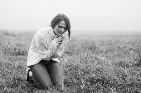 Girl closed her eyes on the knees, praying in a field during beautiful fog. Hands folded in prayer concept for faith, spirituality and religion. Peace, hope, dreams concept
