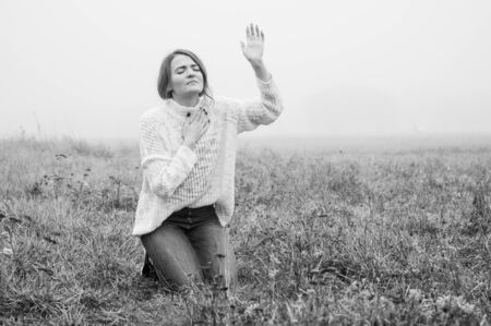 Girl closed her eyes on the knees, praying in a field during beautiful fog. Hands folded in prayer concept for faith, spirituality and religion. Peace, hope, dreams concept 스톡 콘텐츠