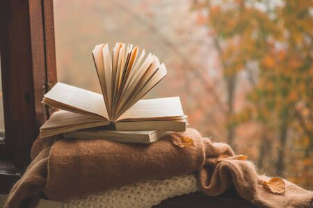 Sweet Home. Still life details in home on a wooden window. Sweaters and candle, autumn decor on the books. Read, Rest. Cozy autumn or winter concept.