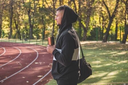 Male model with muscular fit and slim body at the city stadium drinks hot tea. Healthy lifestyle