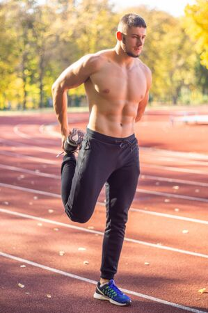 Male model with muscular fit and slim body at the city stadium. Healthy lifestyle