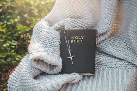 The Bible and the cross lie on a warm sweater. Concept for faith, spirituality and religion. Peace, hope, dreams concept