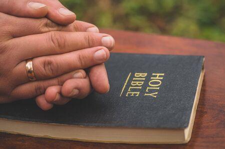 Manos juntas en concepto de oración por fe, espiritualidad y religión. Mujer sosteniendo una cruz en la mano con el telón de fondo de la Biblia. Foto de archivo