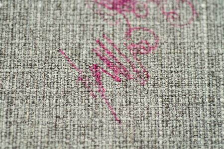 Painted fabric on sofa pink marker. Furniture fabric. Cleaning concept.