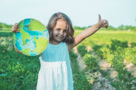 Protection and love of earth. Little girl holding planet in hands against green spring background. Earth day holiday concept. Environmental Conservation