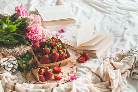 Still life details in home interior of living room. Basket with strawberries Pions flowers and spring decor on the books. Read, Rest. Cozy spring Summer concept.