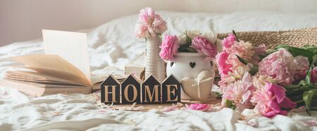 Sweet home. Candle and Vase with roses and peonies flowers and spring decor on the books. Read, Rest. Cozy spring concept.