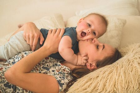 Love and family. Home portrait of a baby boy with mother on the bed. Mom play and kissing her child. Mothers day concept.