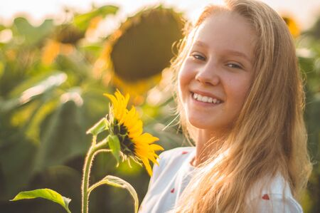 Beautiful young woman in a sunflower field. Portrait of a young woman in the sun. Pollen allergies concept. Outdoors lifestyle happiness. Summer. Standard-Bild