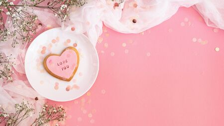 Twigs of gypsophila and cookies with the inscription Love you  on a pink background. Spring background. Love concept Imagens