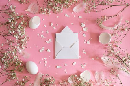Blank greeting card, kraft envelope. Easter eggs and gypsophila flowers on a pink background. Flat lay, top view. Stock Photo