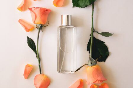 Bottle of perfume with flowers of roses on a white background. Overhead top view, flat lay. Copy space.