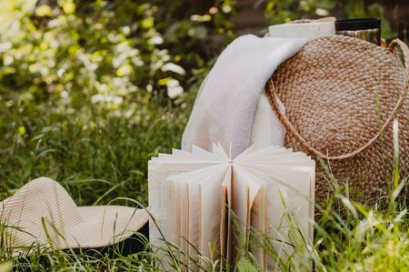 Straw bag, book, hat and thermo cup on a sunny summer day.