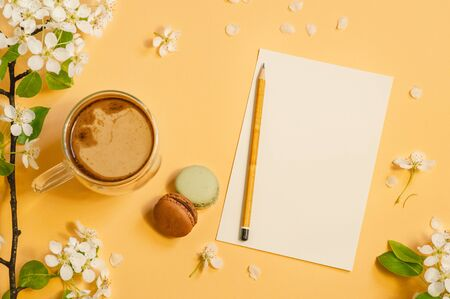 Cup coffee with macaroons and a sheet of white paper on a pastel yellow background. Springtime concept.