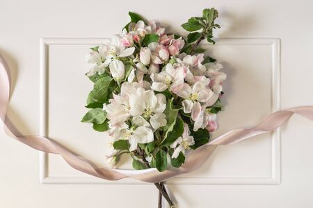 Spring apple blossom branches with pink ribbon over white background. Top view, flat lay