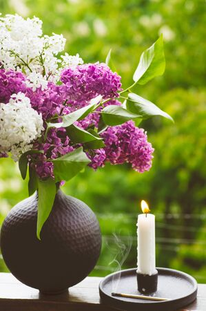 Blooming spring lilac flowers and burning candle in a candlestick. Spring background.