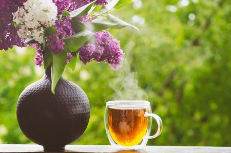 Blooming spring lilac flowers and hot cup tea. Spring background.