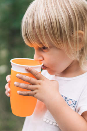 Beautiful little girl with dirty hands drinking from a cup.