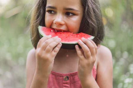 The girl is eating a watermelon. Summer mood.