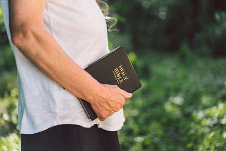 Gray-haired grandmother holds bible in her hands. Reading the Holy Bible in a nature. Concept for faith, spirituality and religion. Peace, hope Stock Photo
