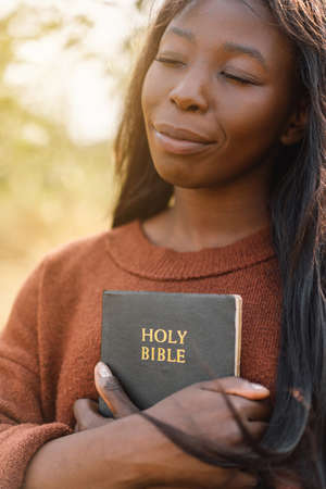 Christian afro girl holds bible in her hands. Reading the Holy Bible. Concept for faith, spirituality and religion. Stock Photo